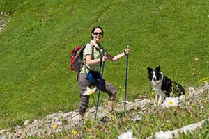 Frau mit Hund beim Bergwandern in der Schweiz